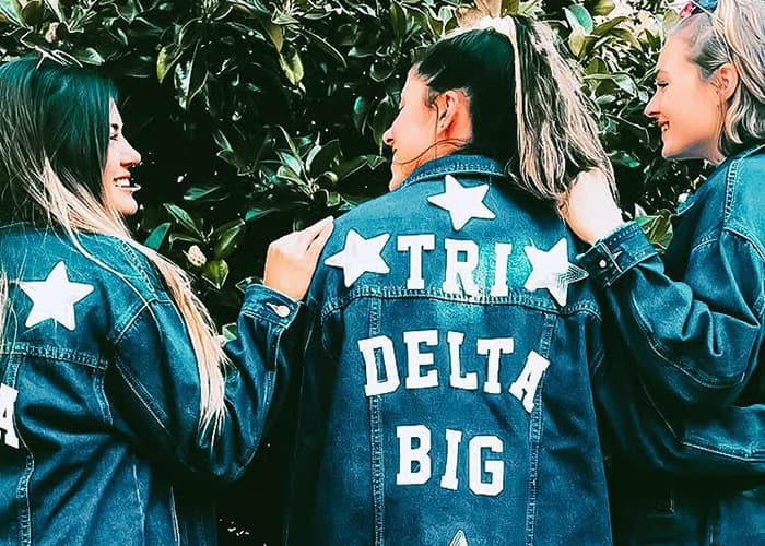Women with denim jackets that read 'Tri Delta Big' on the back.