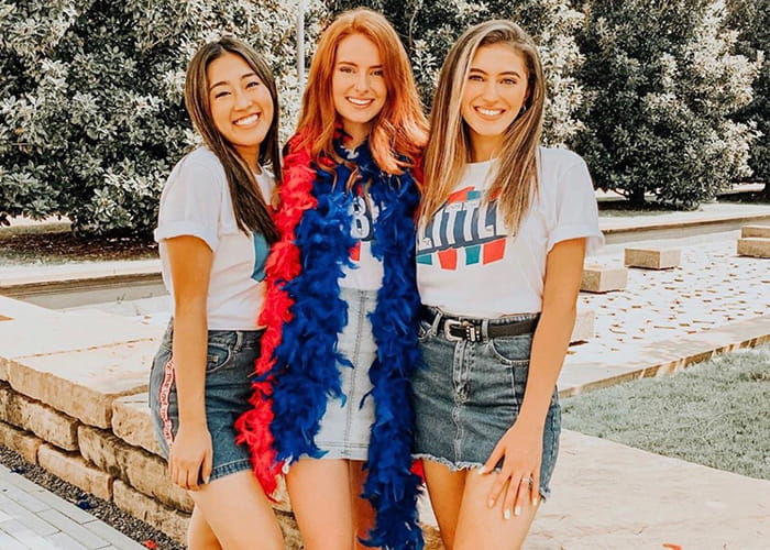 Three women, one wearing a red and blue feather boa.