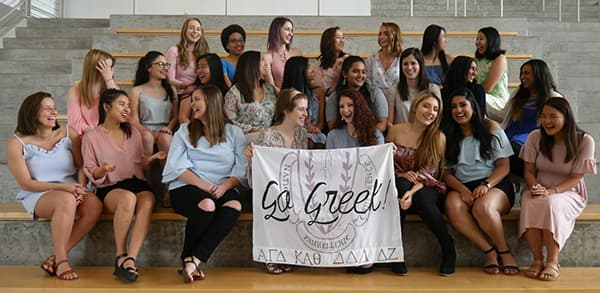 Group photo of women, with two holding a 'Go Greek' banner.
